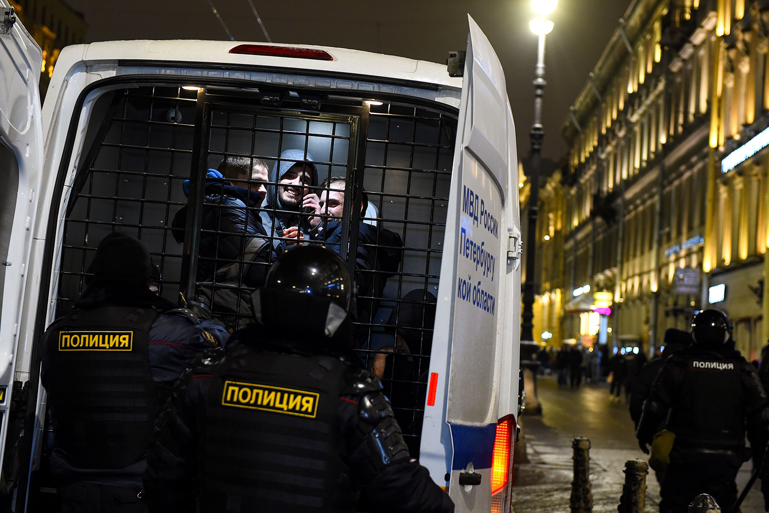 Detained men look out from a police vehicle in downtown St. Petersburg, Russia, on Feb. 2 during a protest against a court ruling that ordered Russian opposition leader Alexei Navalny jailed for nearly three years. OLGA MALTSEVA/AFP via Getty Images
