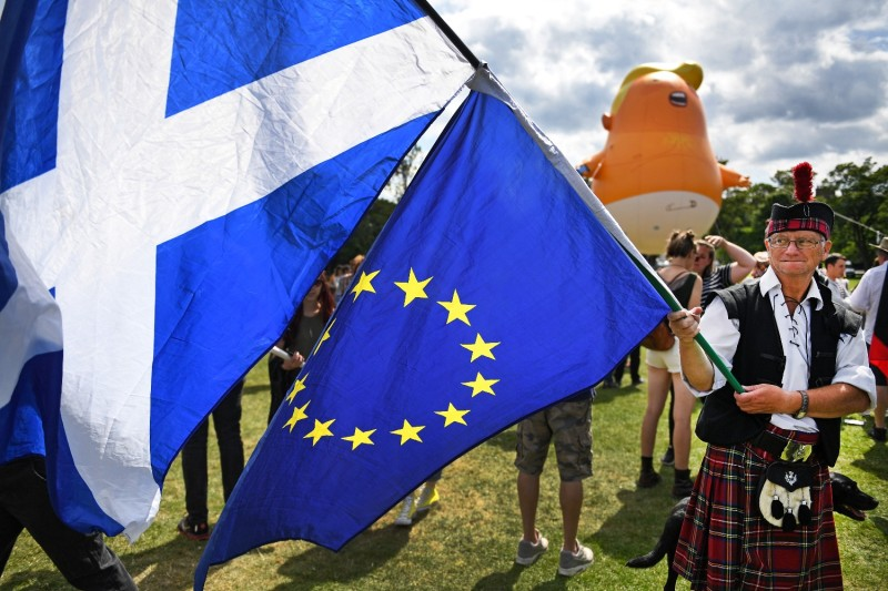 A man dressed in a kilt waves the Scottish flag and the flag of the European Union in Edinburgh, Scotland, on July 14, 2018.