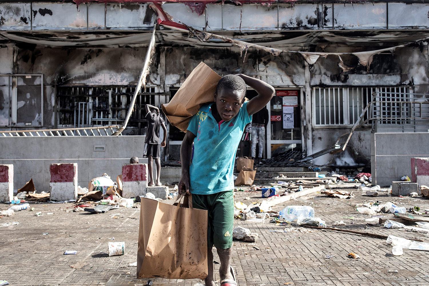 A young boy holds grocery bags as he walks away from a burnt-down and looted Auchan supermarket in Dakar, Senegal, on March 6. The fire took place amid protests following the arrest of opposition leader Ousmane Sonko on rape charges. JOHN WESSELS/AFP via Getty Images