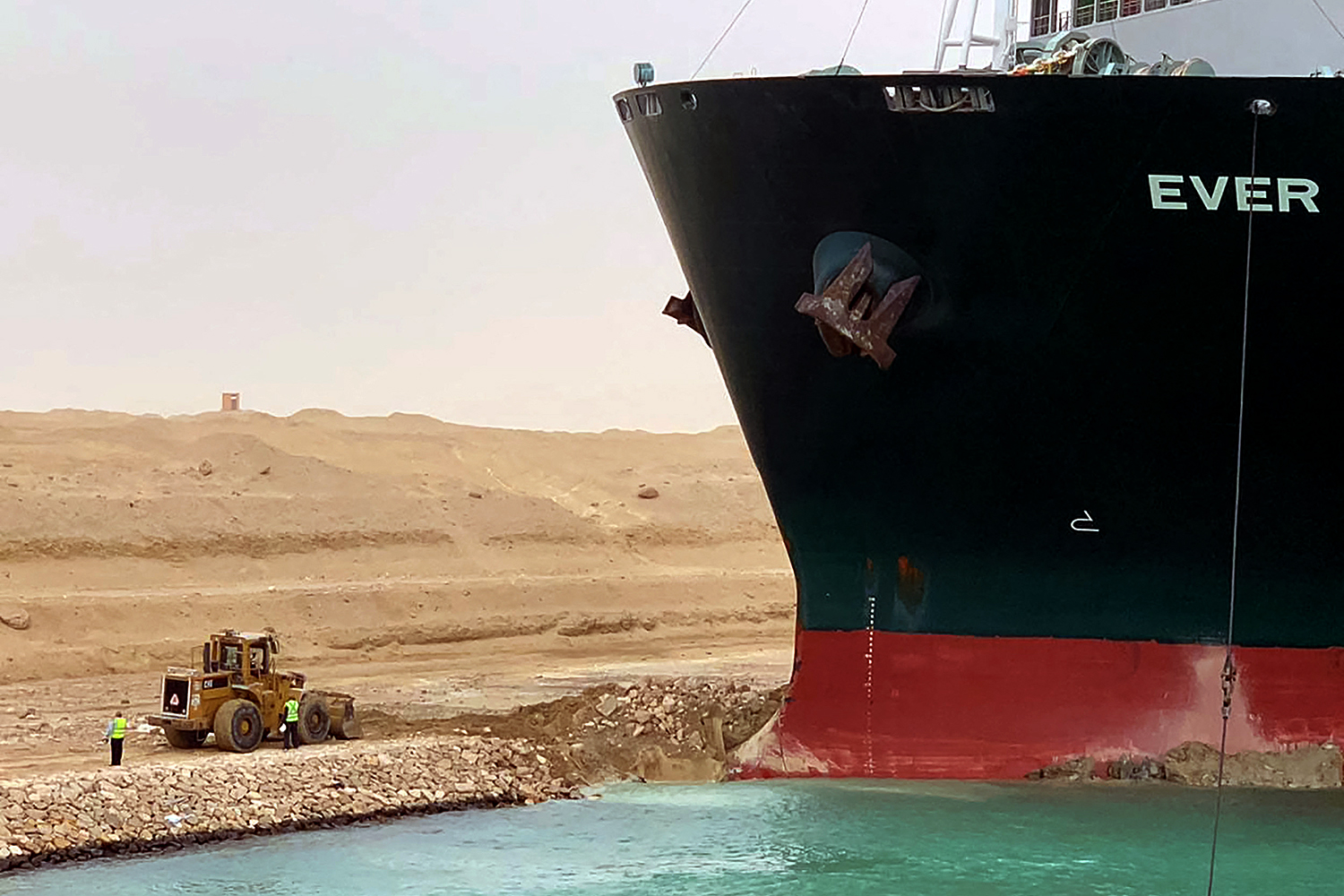 The Taiwan-owned MV Ever Given, a 1,300-foot-long vessel, is lodged sideways in the Suez Canal, impeding all traffic across the waterway, March 24. The giant container ship ran aground after a gust of wind blew it off course, the vessel's operator said. Suez Canal Authority/HO/AFP via Getty Images
