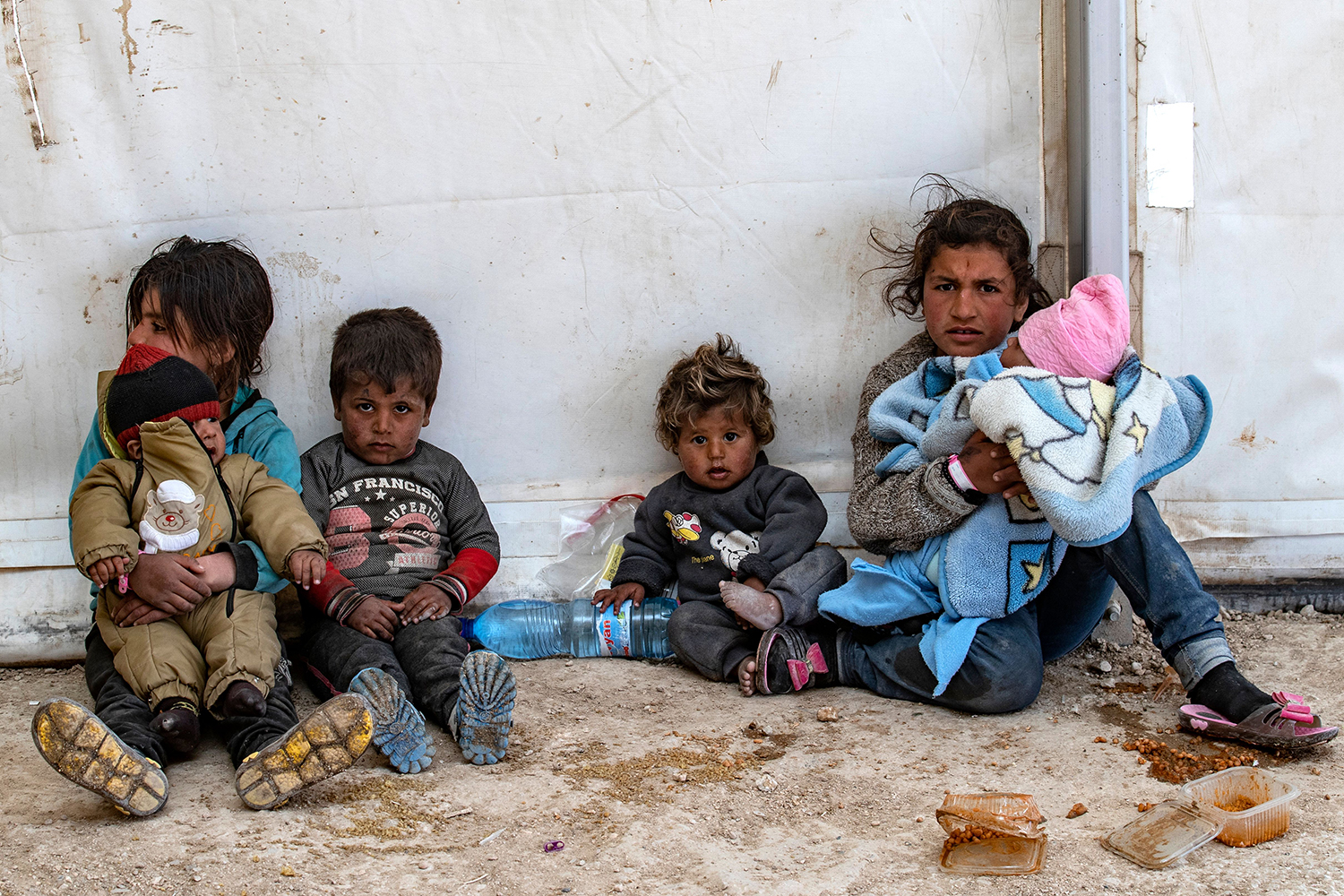 Syrian women and children sit with their belongings as they wait to leave following their release from the Kurdish-run al-Hol refugee camp, which holds suspected relatives of Islamic State fighters, in northeastern Syria on March 18. DELIL SOULEIMAN/AFP via Getty Images