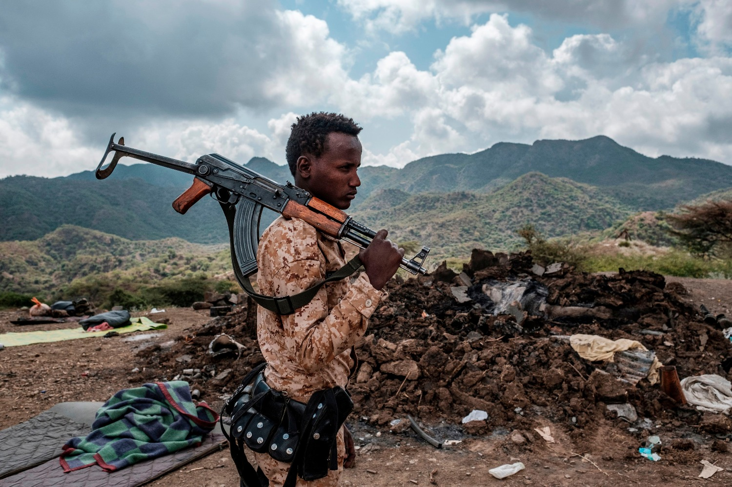 A member of the Afar Special Forces stands in front of the debris of a house in the outskirts of the village of Bisober, Tigray region, Ethiopia, on Dec. 9, 2020.