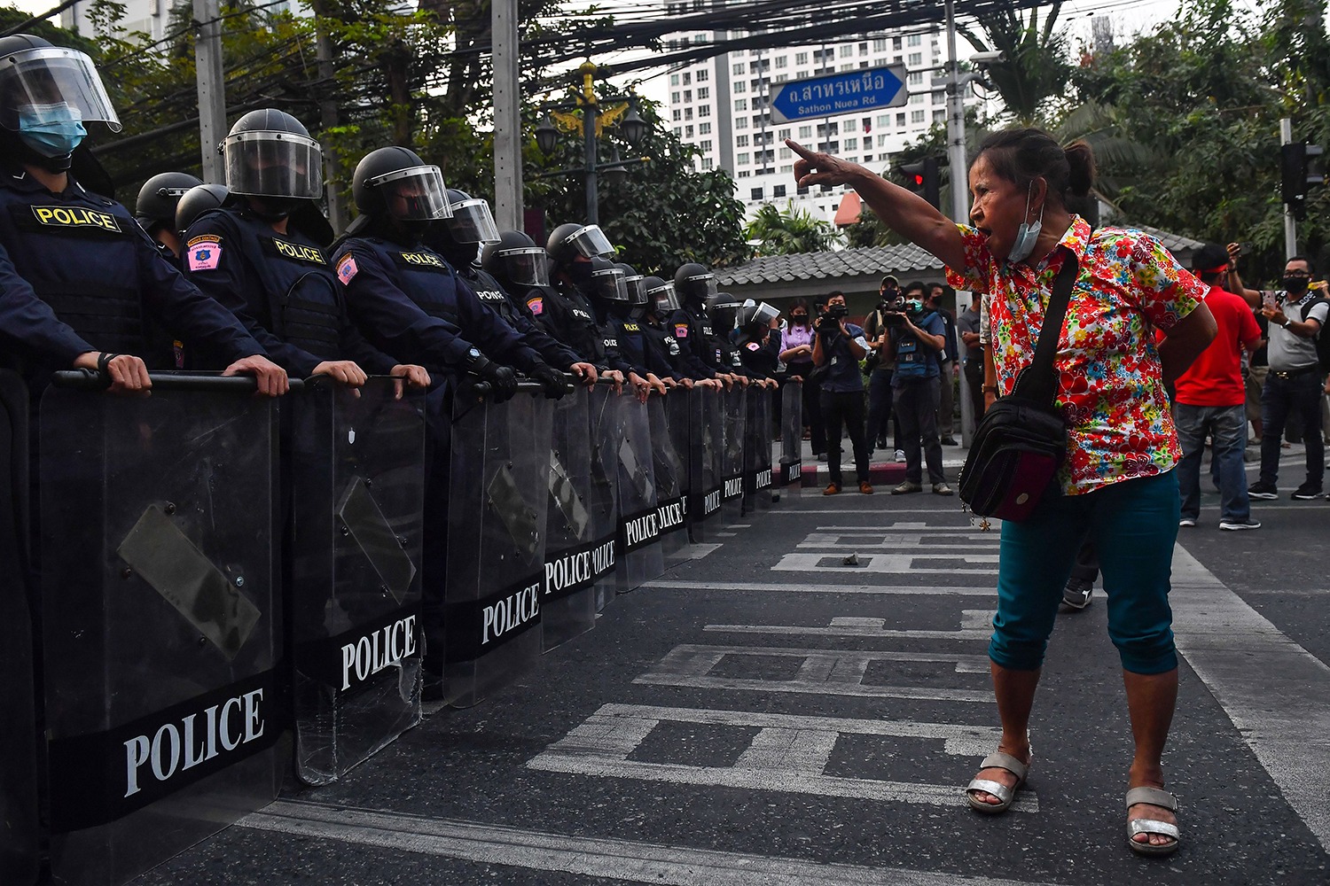 A Thai pro-democracy protester gestures at riot police in Bangkok on Feb. 1, close to where Myanmar migrants were demonstrating after their country's military coup. LILLIAN SUWANRUMPHA/AFP via Getty Images