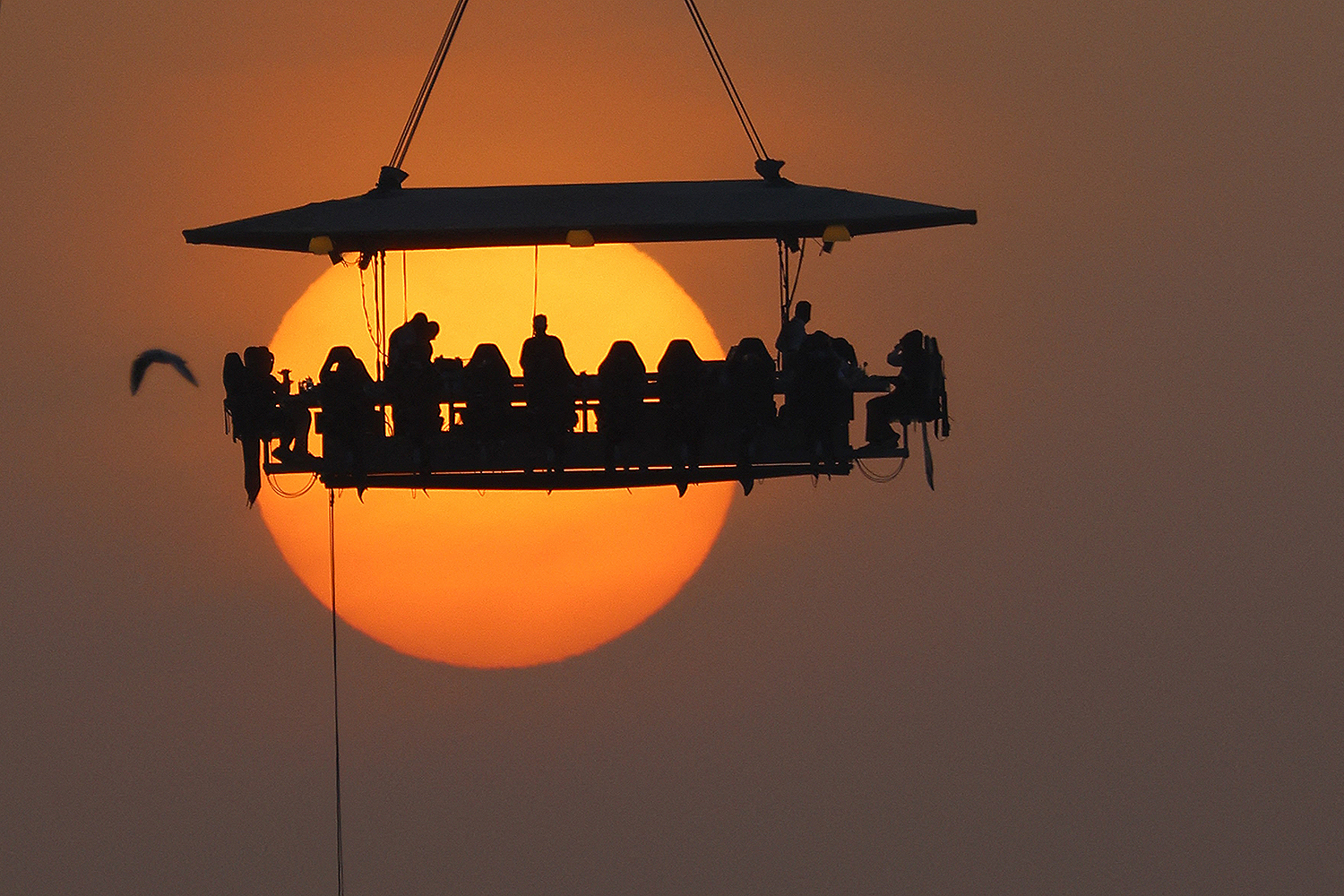 People dine around a table suspended by a crane 55 yards above the ground at the Dinner in the Sky restaurant in Dubai on March 11. GIUSEPPE CACACE/AFP via Getty Images