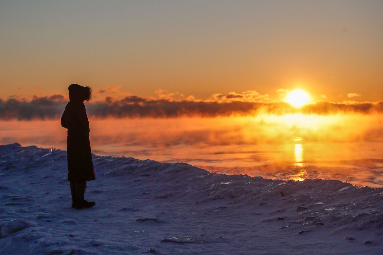 A man walks along Lake Michigan as the sun rises in Chicago, Illinois, on Feb. 7. KAMIL KRZACZYNSKI/AFP via Getty Images