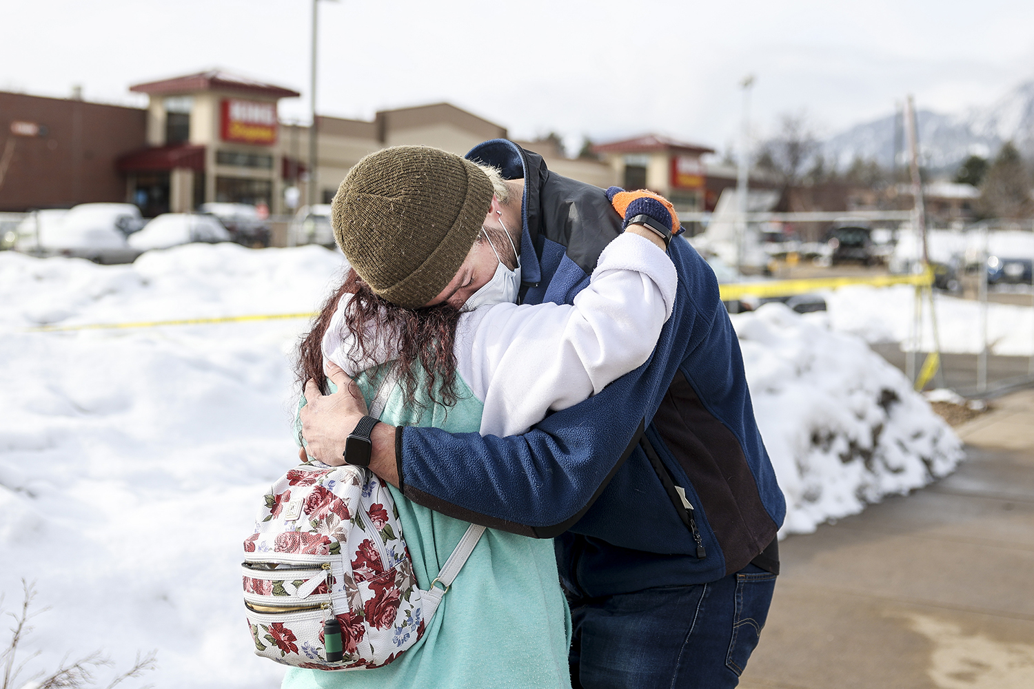 King Soopers employee Brenda Bustamante, left, hugs co-worker Logan Smith—who was inside the grocery store when a gunman opened fire, killing 10—at a makeshift memorial for the victims outside the grocery store in Boulder, Colorado, on March 24. Michael Ciaglo/Getty Images