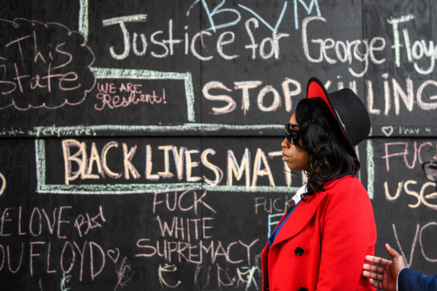 George Floyd's sister Bridgett Floyd walks past messages written by protesters as she leaves the Hennepin County Government Center in Minneapolis on March 8 after the first day of jury selection in the trial of former police officer Derek Chauvin, who is accused of killing George Floyd last May. CHANDAN KHANNA/AFP via Getty Images