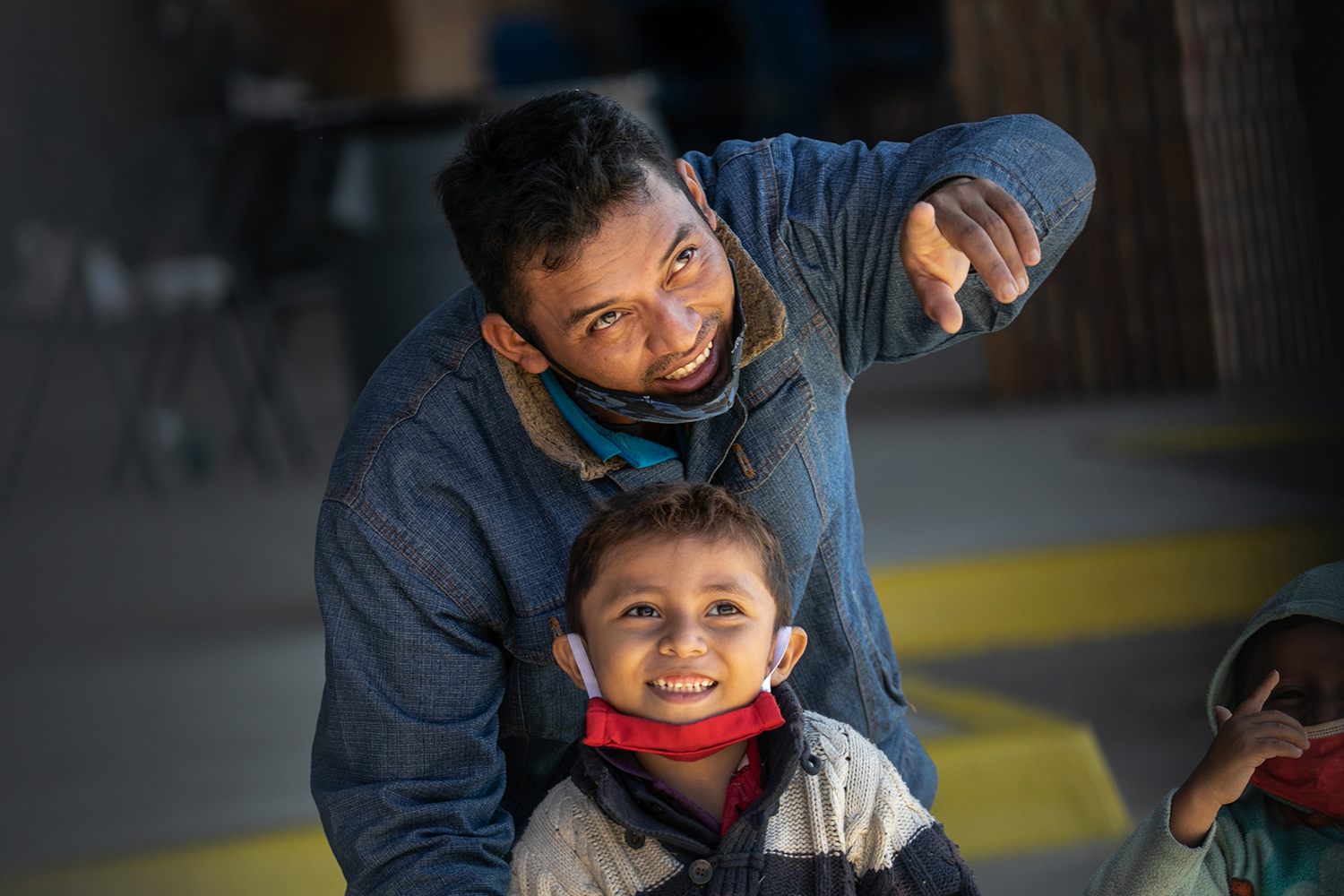 A father points out an outbound bus to his son after they were released by U.S. immigration authorities at a bus station in Brownsville, Texas, on Feb. 24. Immigration officials have begun releasing detained asylum seekers for onward travel within the U.S. pending their asylum court cases. John Moore/Getty Images