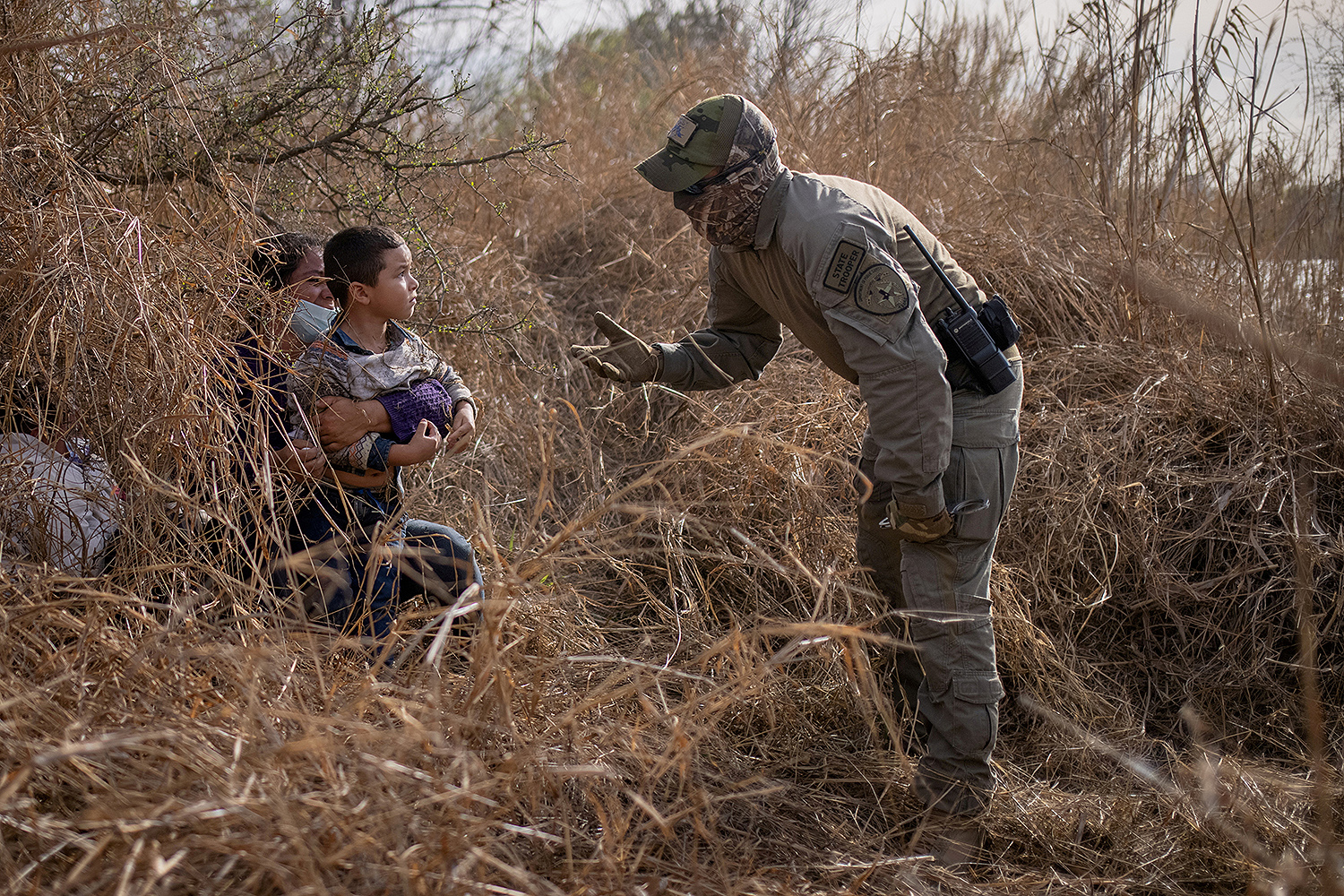 A Texas state trooper asks an asylum-seeking migrant and her 4-year-old son to come out of hiding after the Honduran nationals crossed the Rio Grande into the United States from Mexico on a raft in Penitas, Texas, on March 9. Adrees Latif/REUTERS