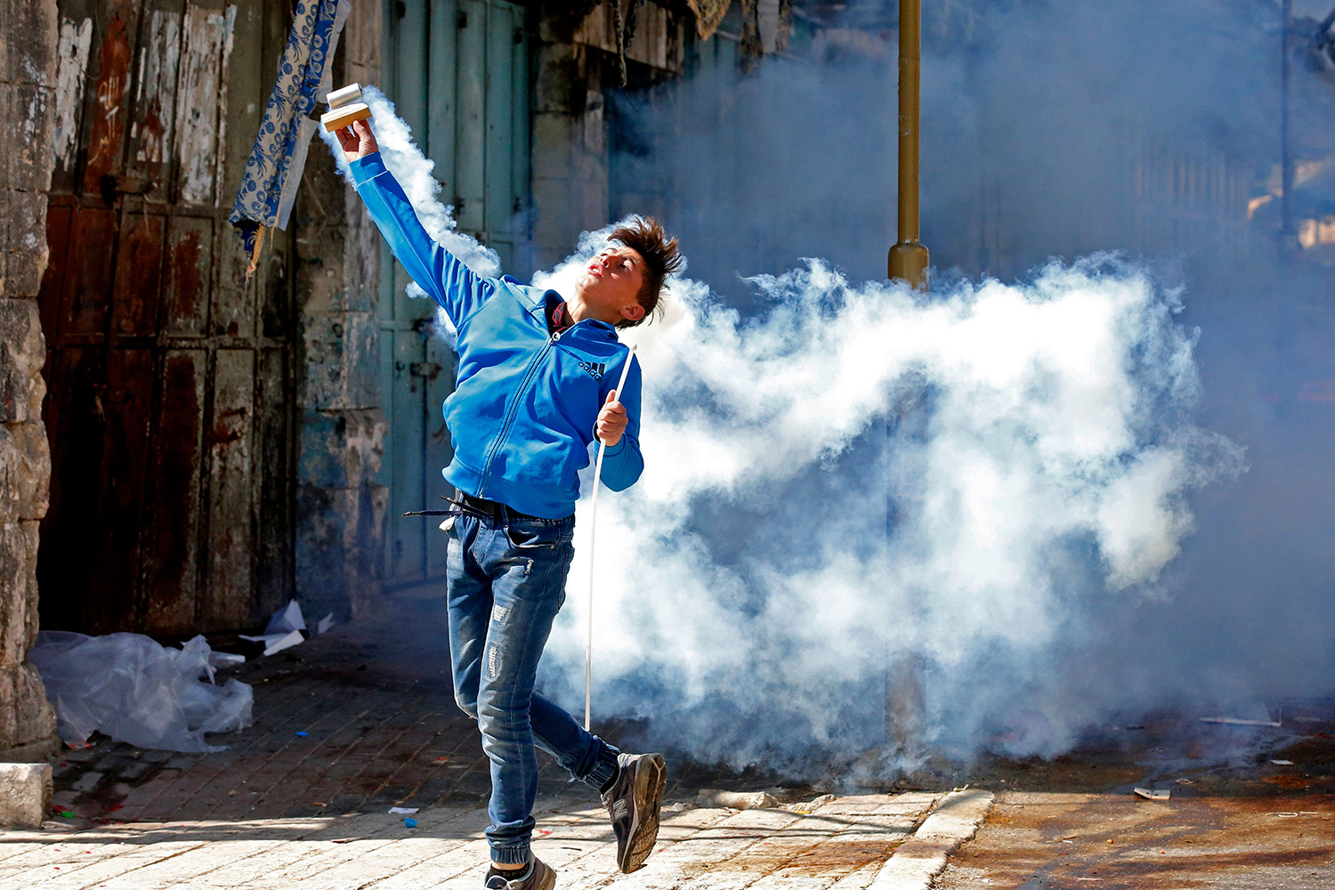 A Palestinian protester throws back a tear gas canister during a demonstration in memory of the 1994 Ibrahimi Mosque massacre, in which a Jewish extremist killed dozens of Palestinian worshippers, in the occupied West Bank city of Hebron on Feb. 26. HAZEM BADER/AFP via Getty Images