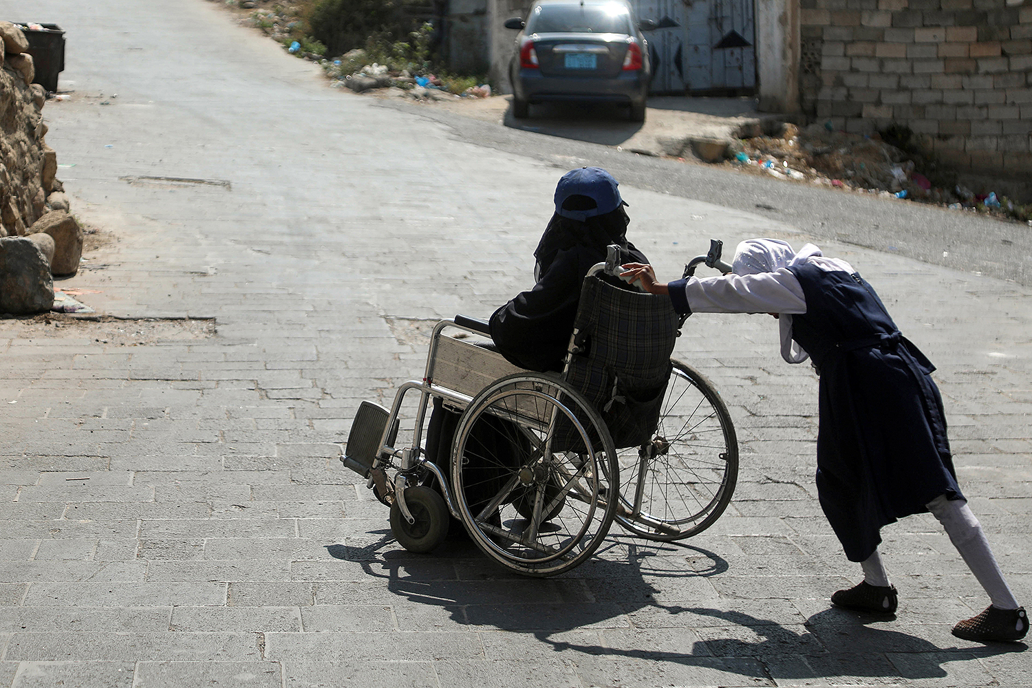 A child of Arwa Naji, disabled after sustaining injuries during a Saudi-led coalition bombardment on her neighborhood in 2015, pushes her mother's wheelchair outside an abandoned house in Taez, Yemen, on Feb. 13. AHMAD AL-BASHA/AFP via Getty Images