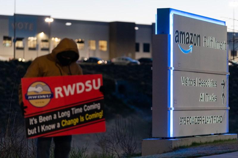 A union representative holds a sign outside the Amazon fulfillment warehouse.