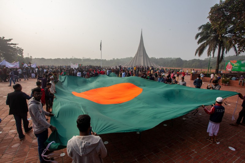 People hold a large national flag during Victory Day celebrations at the National Monument in Savar, Bangladesh, on Dec. 16, 2020.