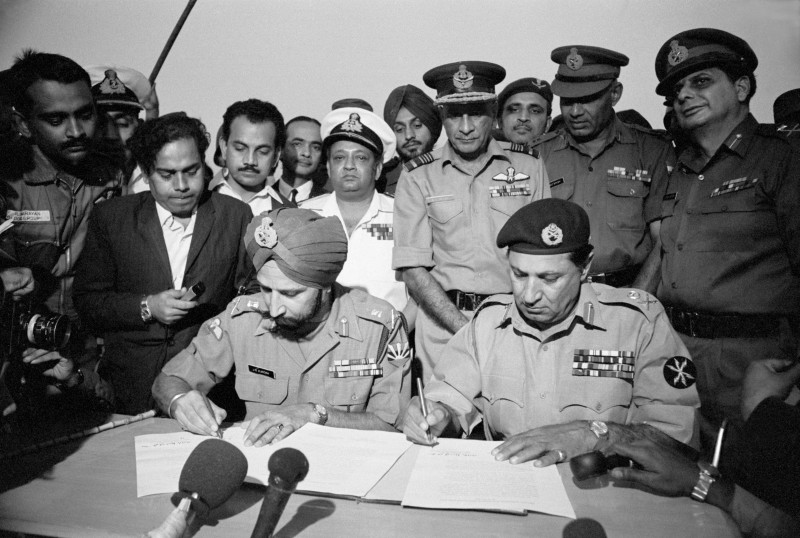 Indian Army Gen. Jagjit Singh Aurora and Pakistani Army Gen. Amir Abdullah Khan Niazi sign the surrender document that would end the war between the two countries and lead to the creation of Bangladesh, in Dhaka on Dec. 16, 1971.