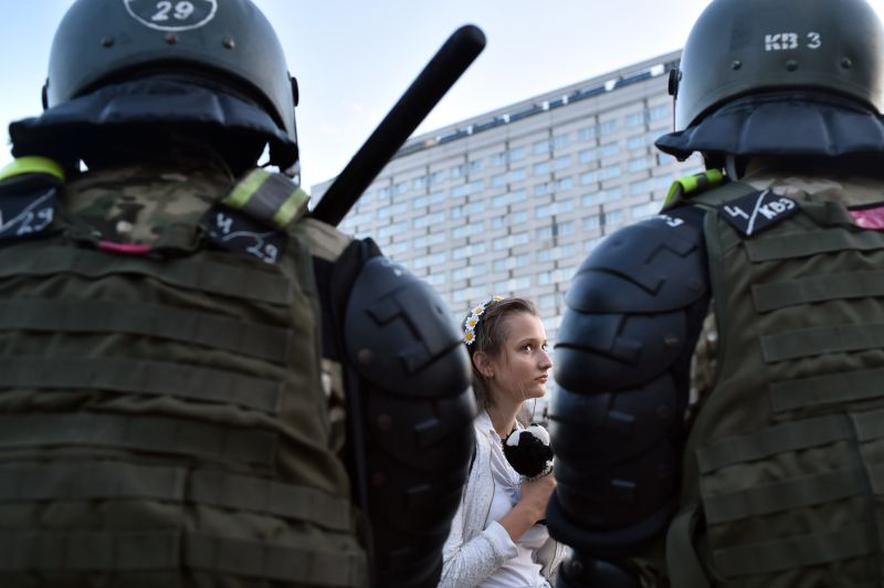 A Belarusian woman walks past security officers during a rally of opposition supporters in Minsk on Aug. 11, 2020.