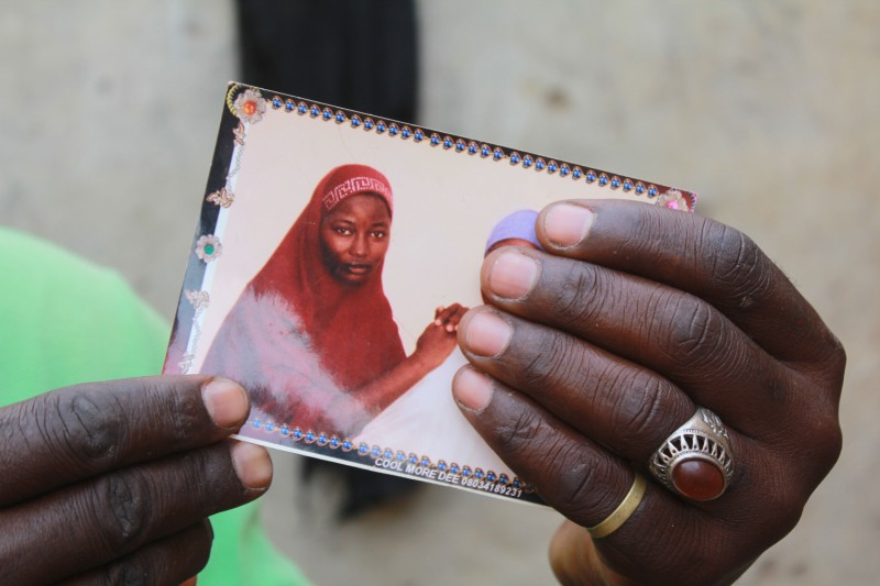 Hands hold up a photo of a young kidnapped Nigerian girl.