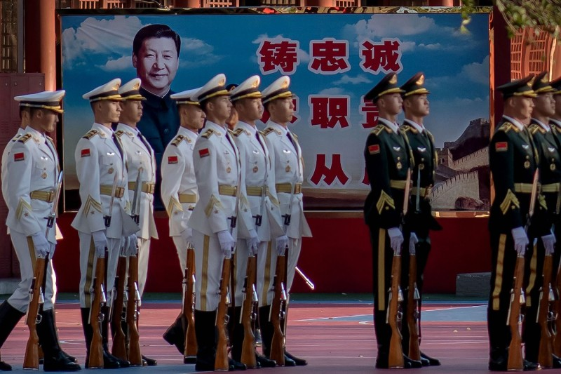Chinese personnel stand in formation next to a portrait of President Xi Jinping in Beijing on Oct. 22, 2020.