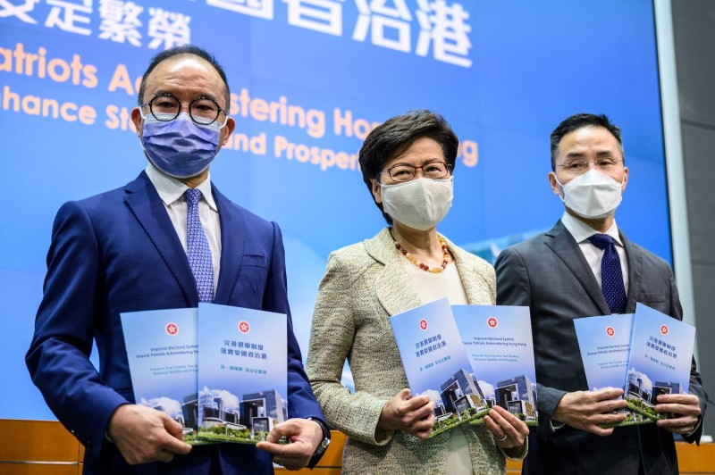 Hong Kong Secretary for Constitutional and Mainland Affairs Erick Tsang Kwok-wai, Chief Executive Carrie Lam, and Permanent Secretary for Constitutional and Mainland Affairs Roy Tang pose before a press conference at government headquarters in Hong Kong on March 30.