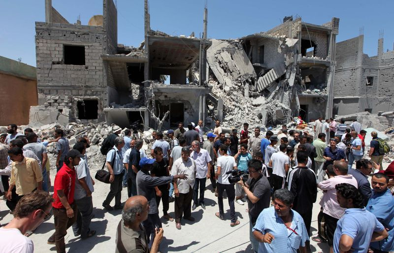 Journalists and locals gather next to the rubble of buildings in Tripoli, Libya.