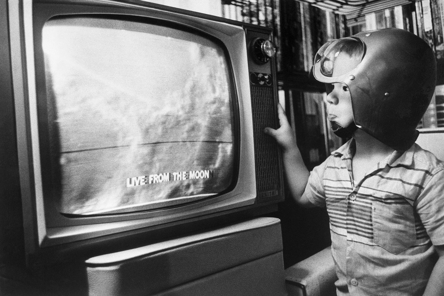 A boy watches the first television images from the moon.