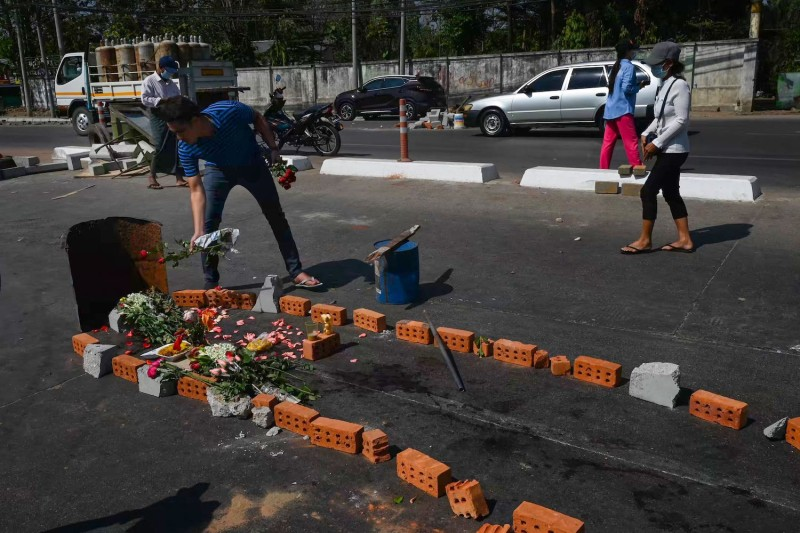 A man lays flowers at the site of a makeshift memorial, where at least five people died from gunshot wounds the day before while attending a demonstration against the military coup, in Yangon on March 4, 2021. (Photo by STR / AFP) (Photo by STR/AFP via Getty Images)