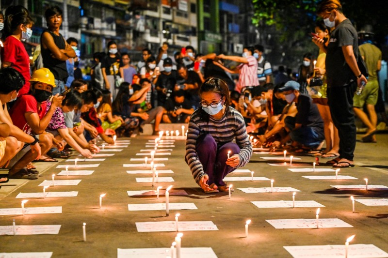 A protester places candles on the ground during a demonstration against the military coup in Yangon, Myanmar, on March 13.