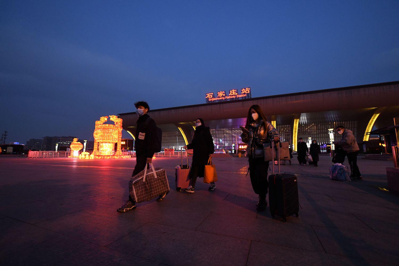 Passengers exit the Shijiazhuang Railway Station in Shijiazhuang, China, on Feb. 8.