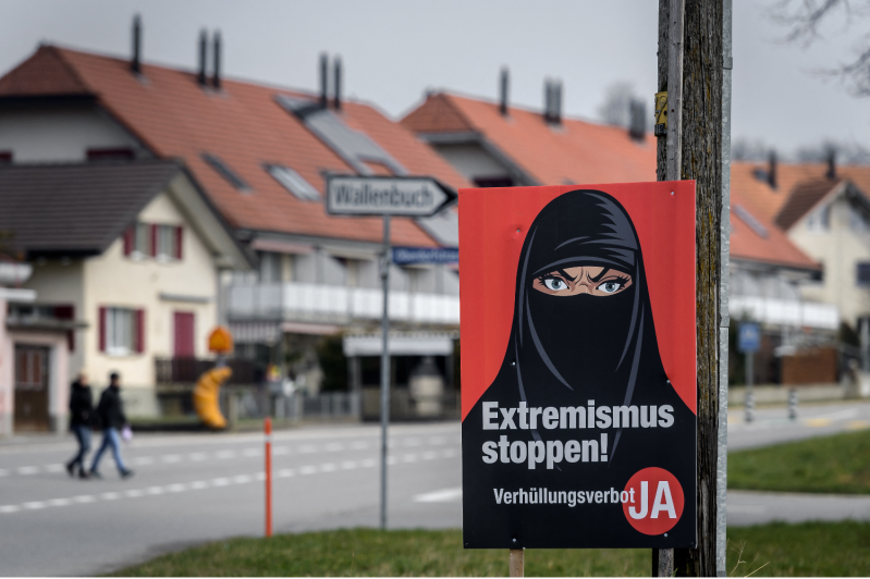 """A campaign poster advocating for a ban on full-face coverings in Biberen, Switzerland, on March 7. The poster reads """"Stop extremism!"""" in German."""