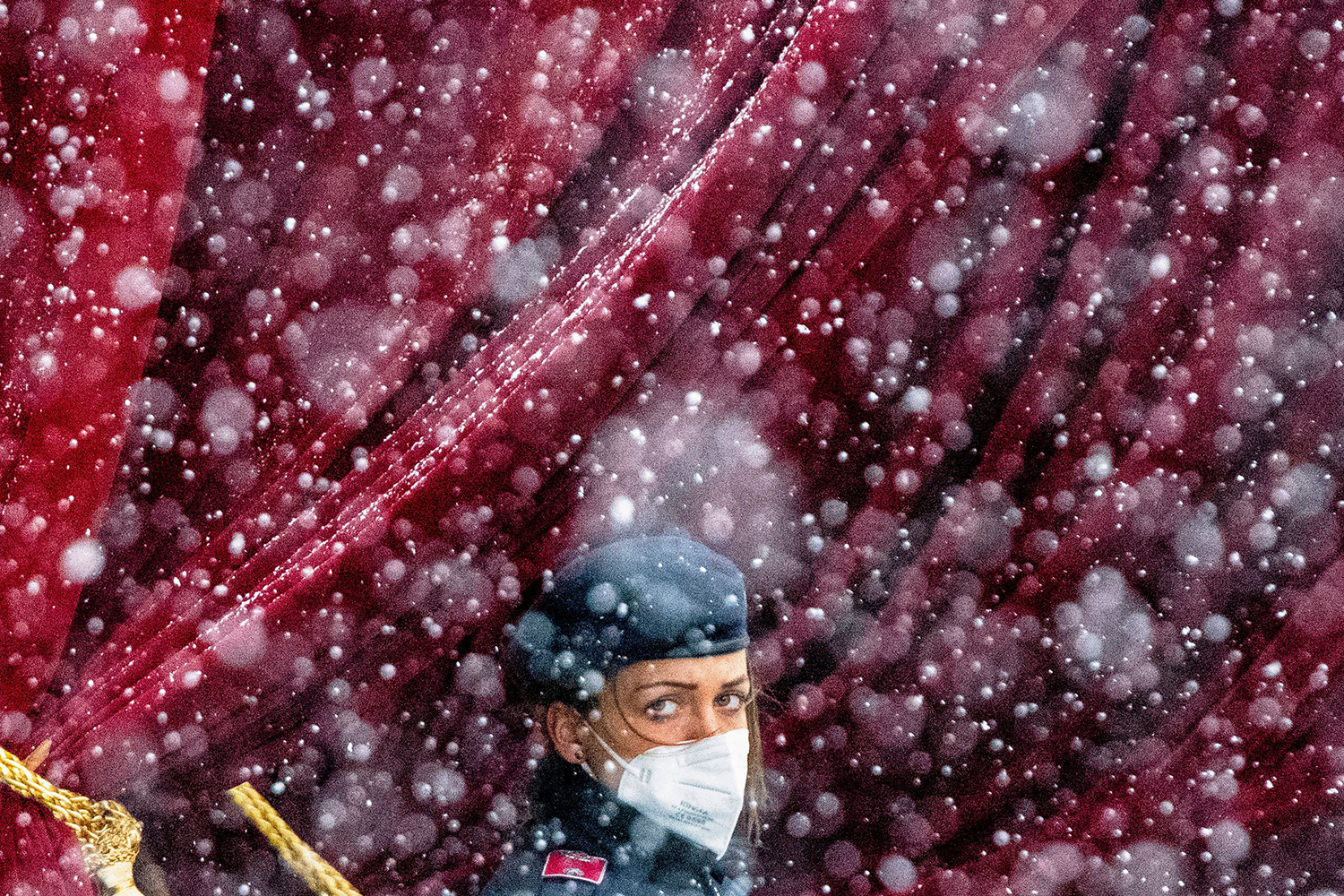 Snow falls as a police officer stands guard near the Grand Hotel in Vienna, where diplomats of the EU, China, Russia, and Iran were holding talks, on April 6. JOE KLAMAR/AFP via Getty Images