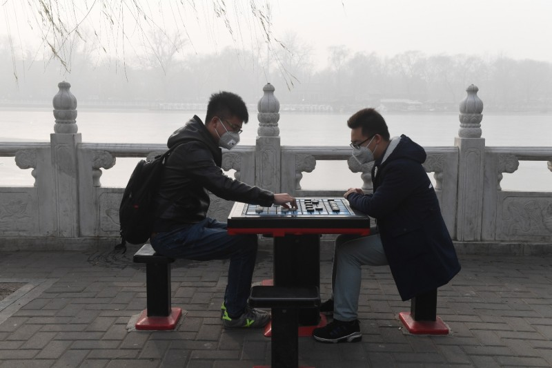 Two men play chess by a smog-shrouded lake.