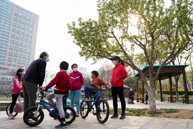 Young Chinese children wear protective masks as they play in a garden in Beijing on March 31, 2020.