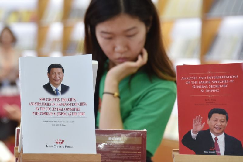 A woman examines a display of books about Chinese President Xi Jinping.