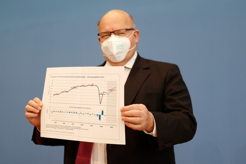 German Economy Minister Peter Altmaier holds a paper with a graph of German GDP in Berlin on Jan. 27.