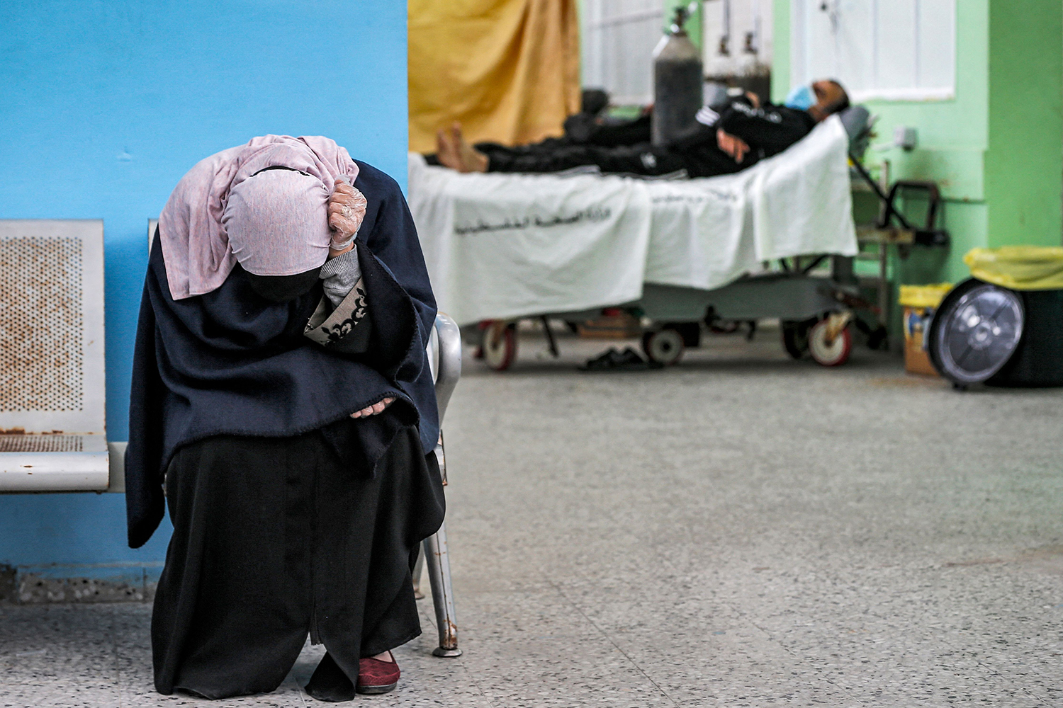 A Palestinian woman waits as her husband, pictured behind her, receives treatment in the COVID-19 intensive care unit of Al-Shifa Hospital in Gaza City on April 7. MAHMUD HAMS/AFP via Getty Images