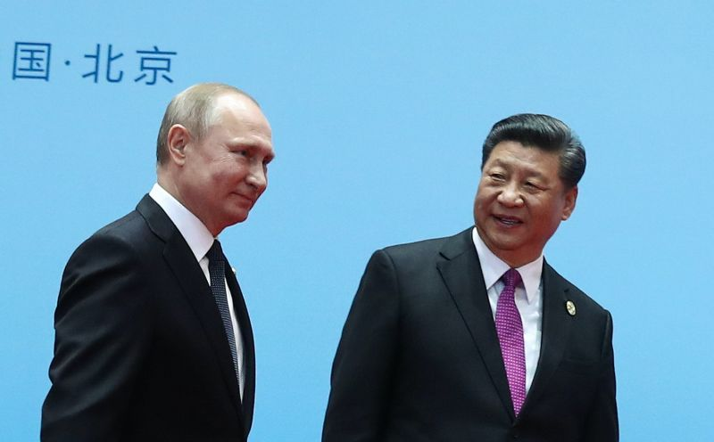 Chinese President Xi Jinping and Russian President Vladimir Putin smile during the Belt and Road Forum.