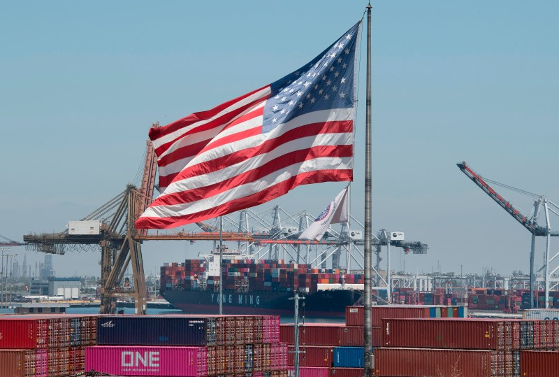 The U.S. flag flies over a container ship.