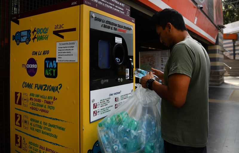A commuter trades plastic bottles to be recycled for transit credit at a reverse vending machine on Oct. 8, 2019 at the Cipro underground metro station in Rome.