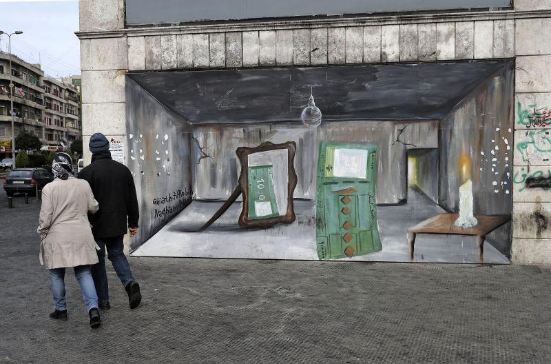 A couple walks past a graffiti mural in Lebanon.