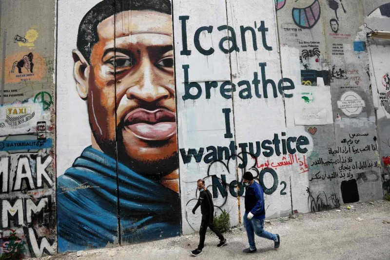People walk past a mural showing the face of George Floyd on a section of Israel's controversial separation barrier in the city of Bethlehem in the occupied West Bank on March 31.