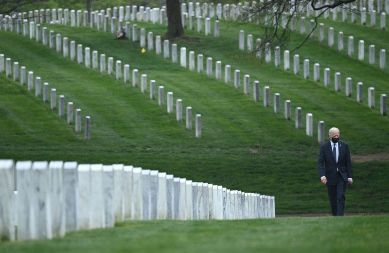 Joe Biden walks through Arlington National cemetery to honor fallen veterans of the Afghan conflict in Arlington, Virginia on April 14, 2021.