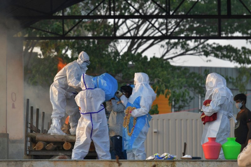 Family members and relatives wearing protective gear carry the body of a victim who died of the Covid-19 coronavirus towards a pyre at an open crematorium in Bangalore on April 26, 2021.