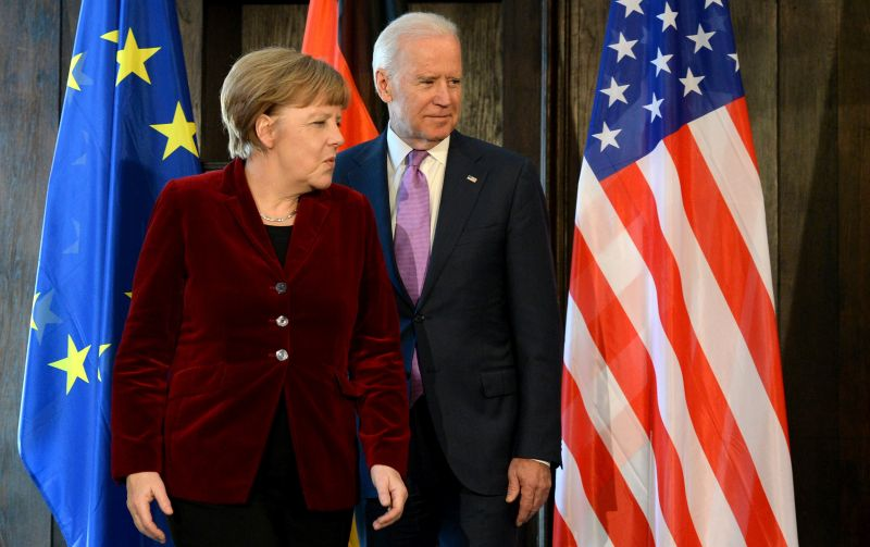 Angela Merkel and Joe Biden pose for photographers prior to their trilateral talks during the Munich Security Conference in Munich on Feb. 7, 2015.