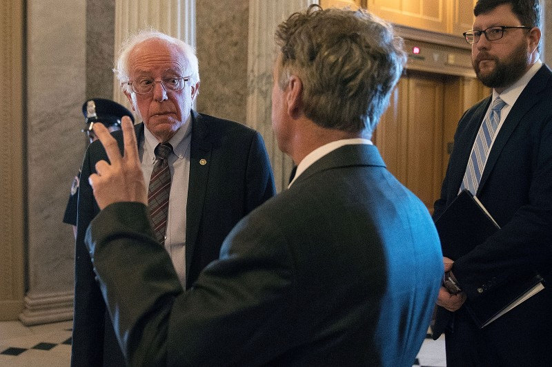 Bernie Sanders talks with Rand Paul as they head to the Senate Chamber for a vote on April 26, 2018 in Washington.