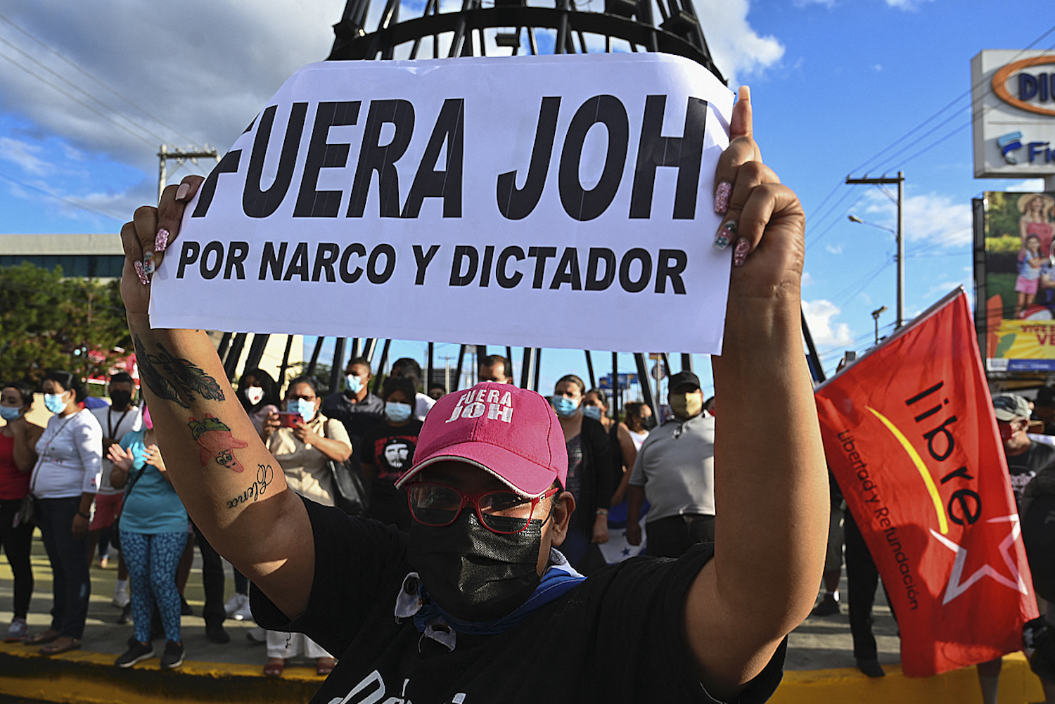 "A woman holds a placard reading ""JOH (Honduran President Juan Orlando Hernandez) Out"" as supporters of the opposition celebrate the sentencing of Juan Antonio Hernandez in Tegucigalpa, on March 30."