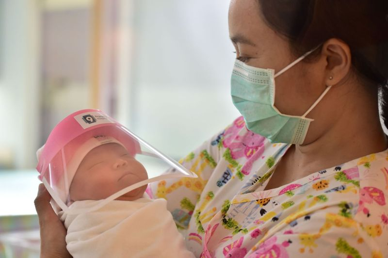 A nurse holds a newborn baby wearing a face shield in an effort to halt the spread of COVID-19, at Praram 9 Hospital in Bangkok, on April 9, 2020.