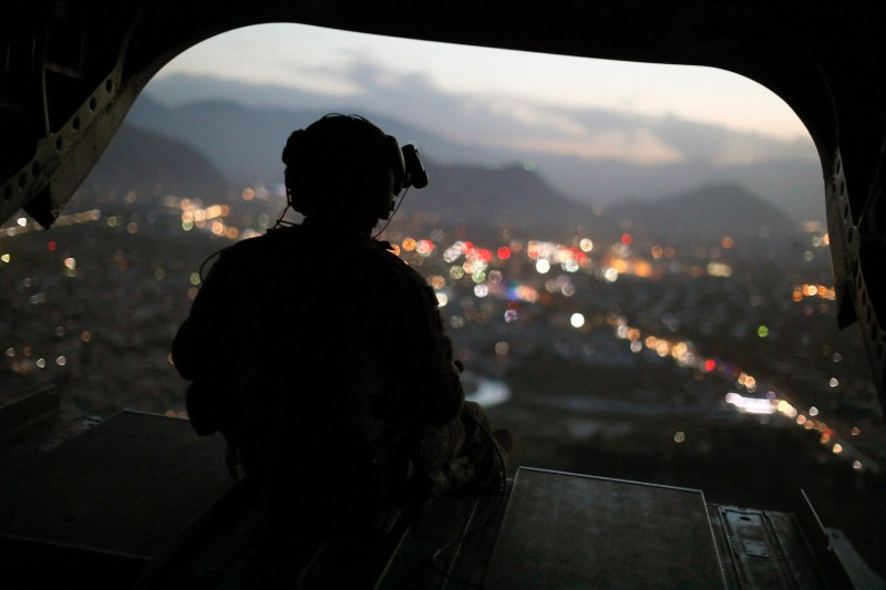 A U.S. Army helicopter crewman mans a gun on the rear gate as it departs Resolute Support headquarters in Kabul on April 24, 2017.