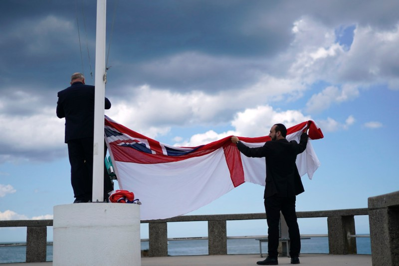 The Royal Navy flag is hoisted during preparations for a commemoration event on the 75th anniversary of the D-Day landings in Arromanches-Les-Bains, France, on June 6, 2019.