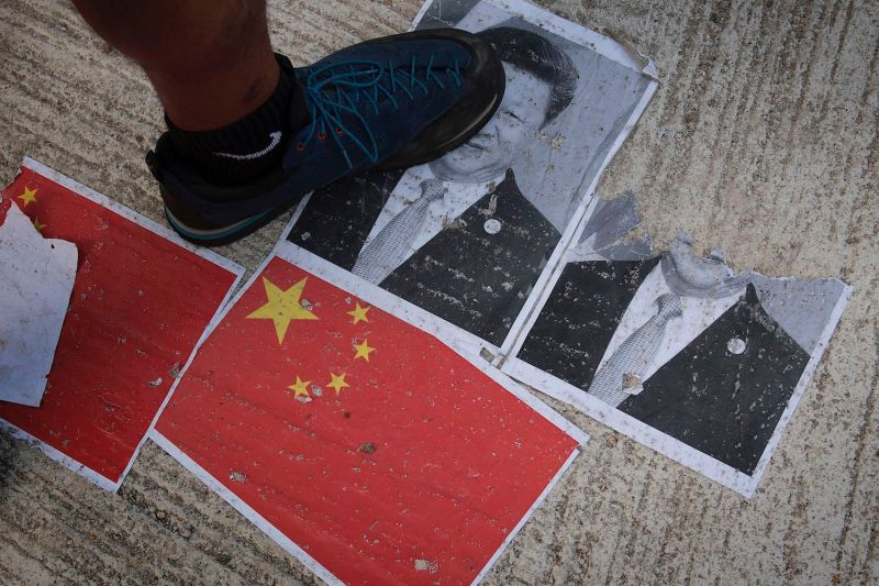 Protesters walk on an image of Chinese President Xi Jinping in the Causeway Bay area in Hong Kong on Oct. 1, 2019.