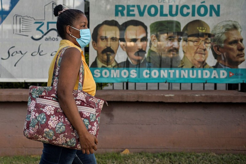 A woman wearing a face mask walks by a banner with pictures of leaders of the Cuban Revolution and President Miguel Diaz-Canel, in Havana on March 3.