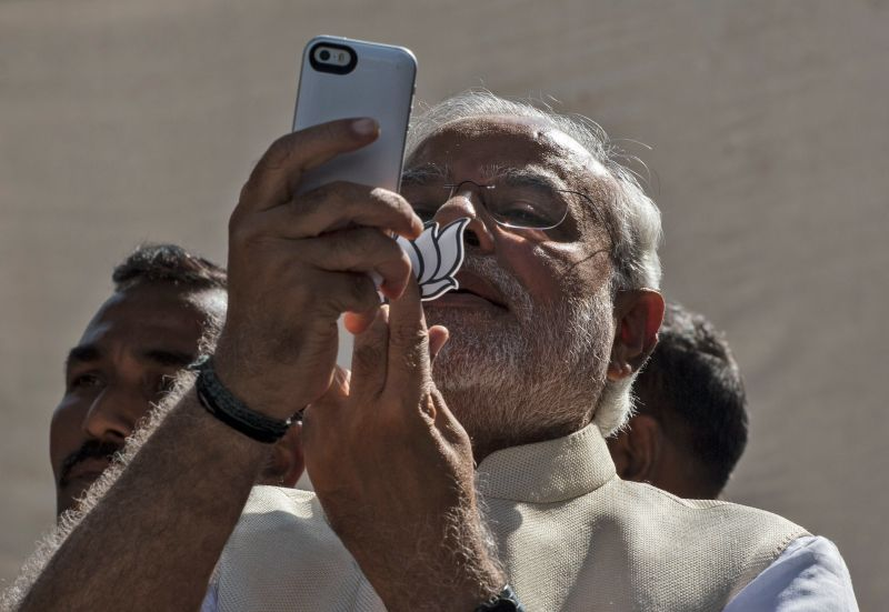 Bharatiya Janata Party leader Narendra Modi takes a selfie with his mobile phone after voting at a polling station in Ahmedabad, India, on April 30, 2014.